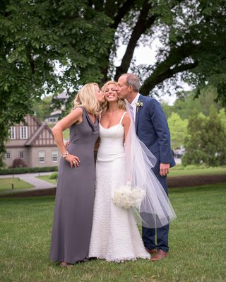 mother-of-the-bride-and-father-of-the-bride-kiss-bride-on-cheek