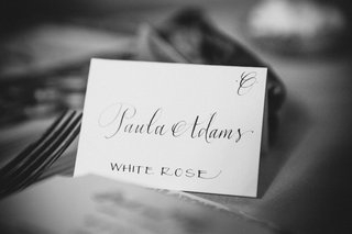 black-and-white-photo-of-a-wedding-reception-escort-card-with-calligraphy-and-flower-table-name