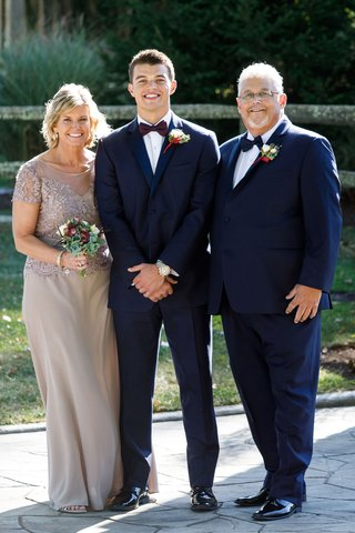 groom-in-navy-blue-suit-with-burgundy-bow-tie-with-father-of-groom-and-mother-in-champagne-taupe
