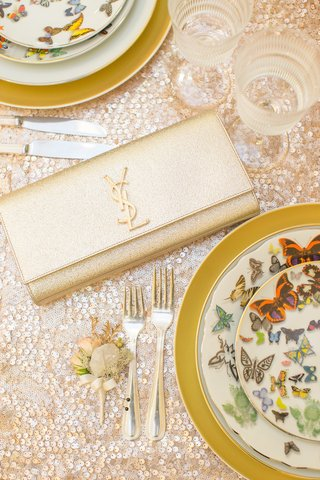 yves-saint-laurent-gilt-clutch-on-sequined-tablecloth-with-christian-lacroix-china-at-wedding