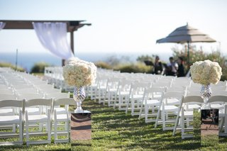 open-air-ceremony-space-reflective-stands-florals-beach-ocean-cliffside-gazebo-glass