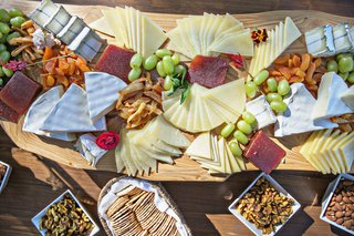 wedding-cheese-plate-crackers-cheeses-fruit-meat-charcuterie-display-on-wood-board-reception