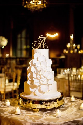four-tiered-cake-with-fondant-frosting-and-oversized-white-flower-trimmed-in-gold-initial-topper