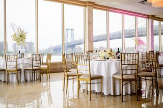 wedding-reception-in-brooklyn-with-view-of-east-river-and-famous-bridges-white-linens-gold-chairs