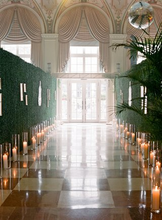 wedding-reception-entrance-checkered-flooring-hedge-wall-candles-photos-long-hall-the-breakers