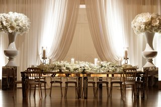 wedding-reception-head-table-white-drapery-urn-oversized-flower-decor-long-white-flower-runner