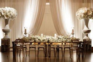 wedding-reception-head-table-white-drapery-urn-oversized-flower-decor-long-white-flower-runner