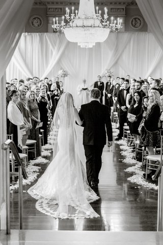 black-and-white-photo-of-bride-being-escorted-by-father-of-the-bride-down-aisle-back-view-biltmore