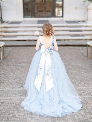 back-of-flower-girl-in-blue-tulle-ball-gown-and-large-floral-sash