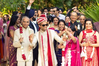 indian-groom-in-ivory-gold-and-red-outfit-and-turban-enters-ceremony-with-his-procession