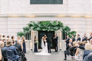 cleveland-museum-of-art-wedding-ceremony-tropical-greenery-arch-modern-decor-guests-oval-lucite