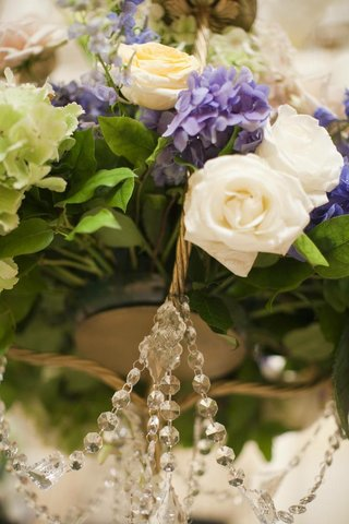 wedding-arrangement-of-purple-white-and-green-flowers-with-greenery-and-crystals