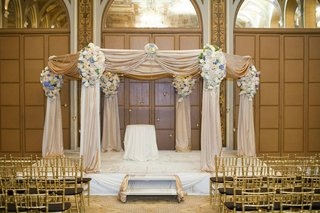 chuppah-draped-in-light-golden-fabric-decorated-with-white-and-blue-flower-arrangements-and-crystals