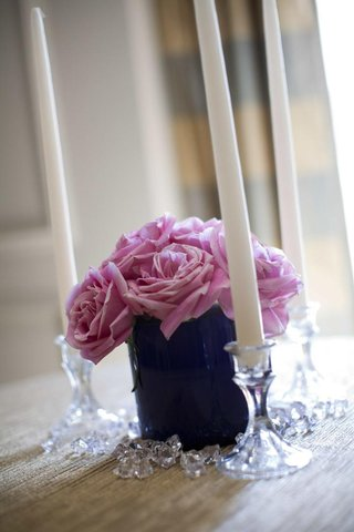 small-arrangement-of-light-purple-flowers-surrounded-by-three-taper-candles-in-crystal-holders
