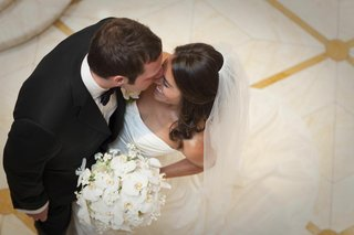 bride-in-a-romona-keveza-dress-veil-and-bouquet-of-white-flowers-with-groom-in-black-tuxedo