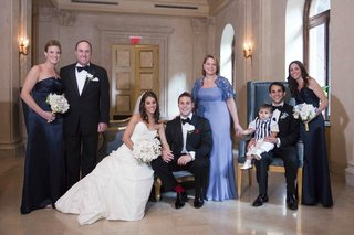 bride-in-a-romona-keveza-dress-veil-and-white-bouquet-with-groom-in-black-tuxedo-with-family