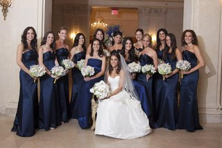 bride-in-a-romona-keveza-dress-and-veil-with-bridesmaids-in-long-dark-blue-badgley-mischka-dresses