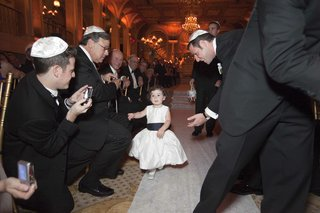 flower-girl-walks-down-the-aisle-in-a-sleeveless-satin-gown-with-a-black-sash