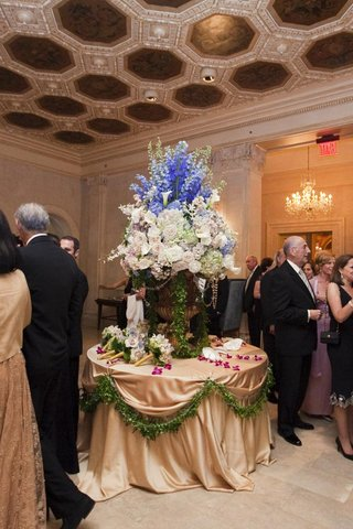 wedding-reception-table-with-golden-tablecloth-and-urn-full-of-white-blue-and-blush-flowers