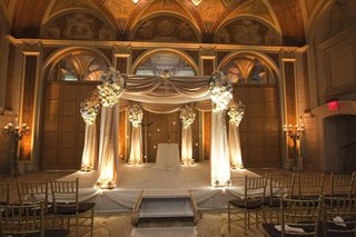 chuppah-draped-in-light-golden-fabric-decorated-with-white-and-blue-flower-arrangements