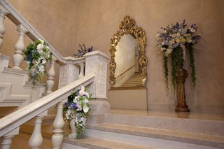 arrangements-of-purple-light-pink-white-flowers-adorn-stairway-at-the-plaza-for-a-wedding