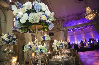 wedding-reception-centerpiece-of-golden-stands-with-white-blue-and-green-flowers