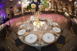 wedding-reception-table-with-gold-rimmed-plates-golden-napkins-candles-and-flowers