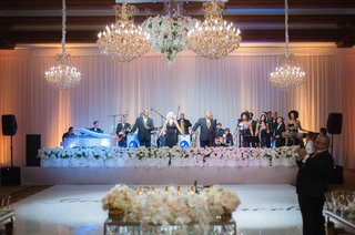 bonnie-foster-productions-at-wedding-reception-dance-floor-chandeliers-white-flowers-around-stage