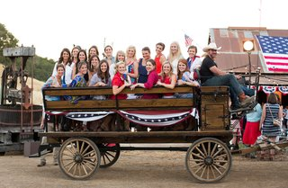 guests-pose-for-photo-in-old-fashioned-wooden-wagon