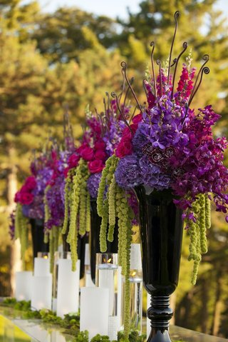 black-vases-with-purple-and-green-flowers-at-ceremony