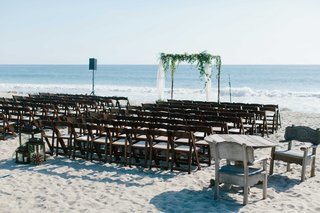 ceremony-space-beach-wood-chairs-arch-greenery-sand-wedding-oceanside-california