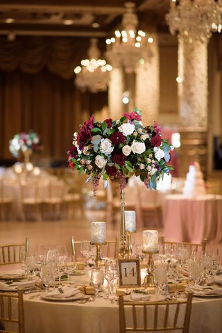 round-table-gold-riser-flower-arrangement-burgundy-green-white-chandeliers-candlelight-gold-chairs