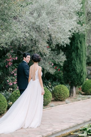 bride-with-illusion-back-wedding-dress-with-tulle-skirt-and-train-walks-down-path-with-groom-in-tux