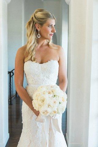 blonde-bride-holding-bouquet-in-monique-lhuillier-lace-wedding-gown