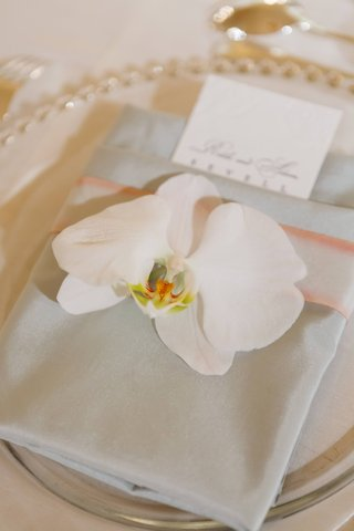 folded-dinner-napkins-with-orchid-place-topper