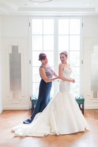 bride-in-trumpet-wedding-dress-with-mother-of-bride-helping-button-in-navy-dress-with-beaded-bodice