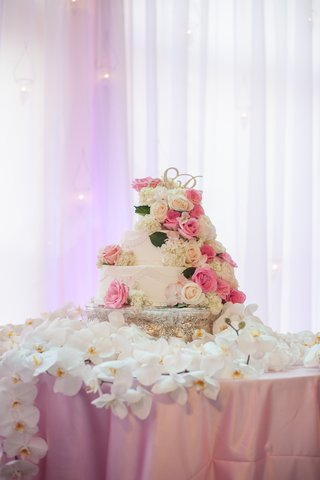 white-cake-with-fresh-roses-on-table-of-orchids