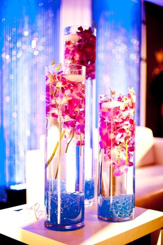 cylindrical-vases-filled-with-pink-orchids-and-candles