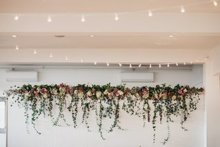 bistro-lights-overhead-indoor-reception-and-photo-wall-topped-with-florals-and-cascading-ivy