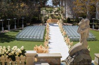 wedding-ceremony-outdoor-monarch-beach-resort-pampas-grass-aisle-runner-statue-stone-gazebo-heaters