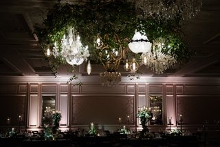 greenery-above-dance-floor-with-several-chandeliers-at-wedding-reception