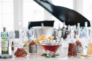 whisky-and-bourbon-bar-at-wedding-reception-in-front-of-piano-glass-decanters-and-botles