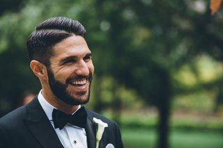 groom-in-bow-tie-and-calla-lily-boutonniere-hair-cut-side-part-with-tuxedo