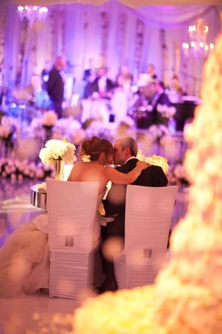 bride-and-groom-kiss-at-sweetheart-table-during-reception