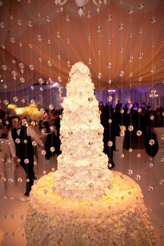 rose-cake-table-with-tall-wedding-cake-behind-crystals