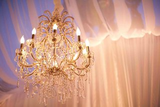 gold-crystal-chandelier-illuminates-wedding-drapery