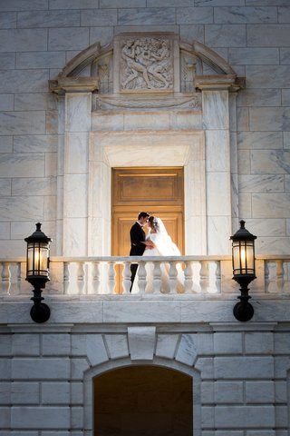 wedding-portrait-bride-and-groom-on-romeo-and-juliet-balcony-lantern-sconces-doors-marble