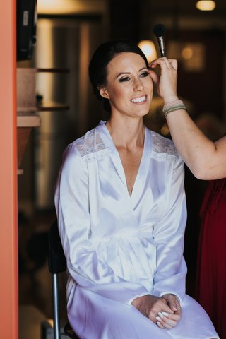 bride-in-white-robe-with-lace-cut-outs-smiles-while-makeup-is-applied
