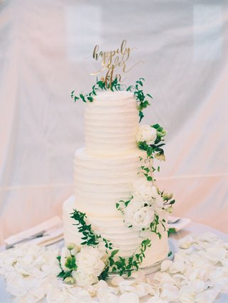 wedding-cake-with-buttercream-fresh-white-flowers-greenery-gold-happily-ever-after-cake-topper