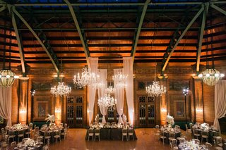 wedding-reception-tall-drapery-crystal-chandeliers-with-wood-walls-and-rustic-elements